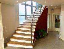 Moderne Treppe – Holzstufen in Eiche Stabverleimt = mit weißen Stoßbretter = mit Edelstahlgeländer = mit LED Lichtleiste im Stufenvorsprung