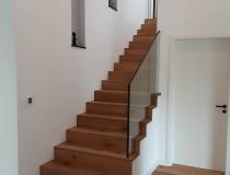 Moderne Treppe – Holzstufen mit Glasgeländer = Stufen in Faltwerk Ausführung – Asteiche = Sicherheits-Glasgeländer eingefräst = im OG mit Brüstungsgeländer Anthrazit-lackiert = Montage auf Betontreppe