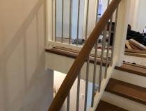 Stufen und Geländer auf Betontreppe = Stufen und Handlauf in Antik-Eiche geölt = halbgewendelt – Stoßbretter und Geländer in weiß lack RAL-9010 = mit V2A-Edelstahlstäbe