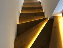 Massive Holz-Stufen in Ast-Eiche auf Betontreppe – 2x viertel gewendelt + Setzstufen in weiß lack 9010 + mit LED-Beleuchtung + mit Mauerabdeckung